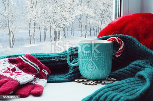 istock Winter background. Cup with candy cane and gloves on windowsill 888698860