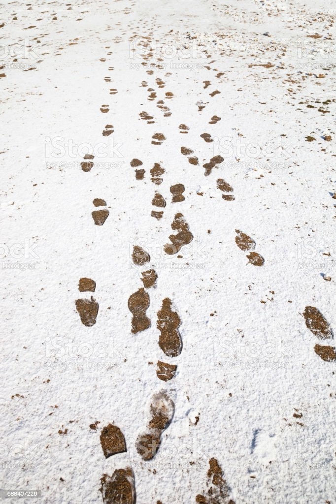 winter background with foot steps on snow ground. stock photo
