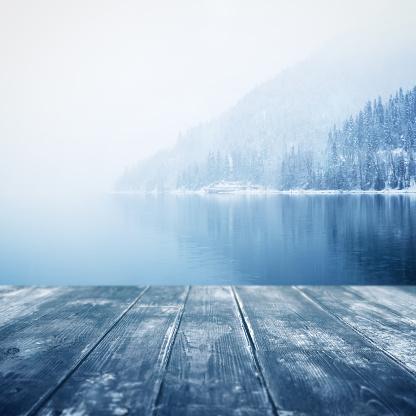 winter background. Wooden floor and defocused winter landscape on background