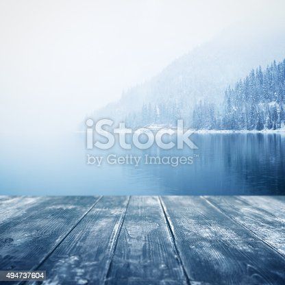 winter background. Wooden floor and defocused winter landscape on background