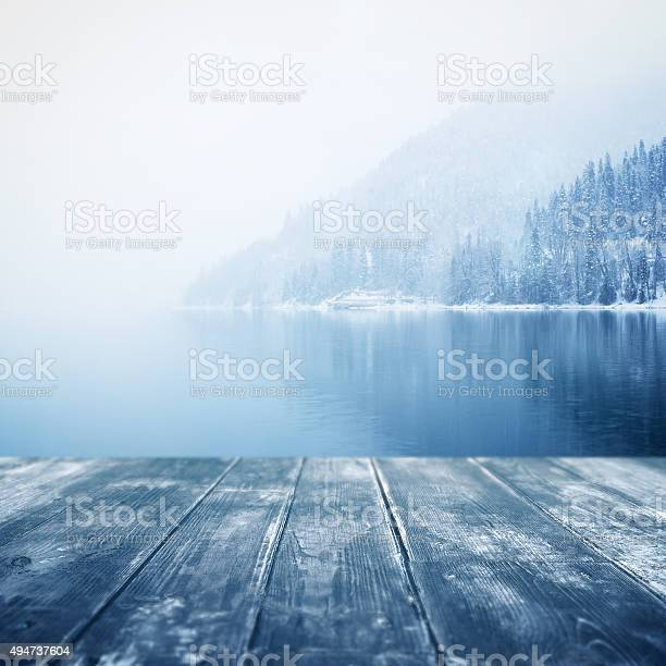 Photo of Winter background. Wooden floor and defocused winter landscape on background