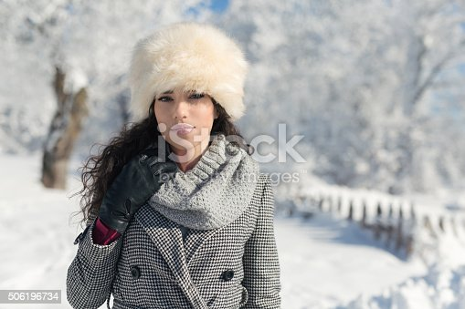 Portrait of a fashionable young woman enjoying a beautiful winter day in the mountains.