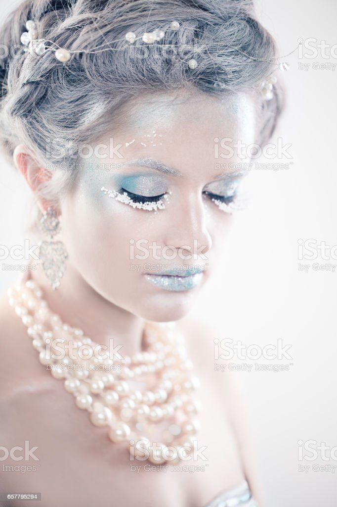 Winter Beauty Woman Fashion Model. Beautiful Girl with Snow Makeup and Hairstyle. Closed Eyes. New Year's Party Make-up stock photo