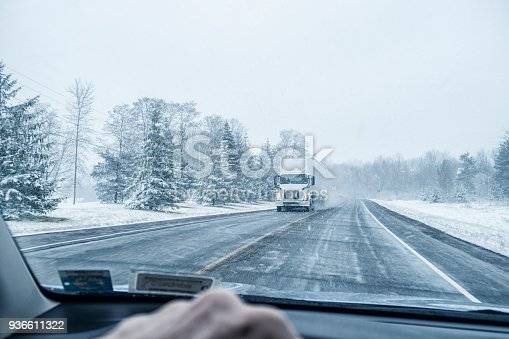 Speeding car driver point of view looking through the windshield at a semi tractor trailer truck with illuminated headlights approaching rapidly from the opposite direction on a remote rural New York State Finger Lakes region highway during a January winter blizzard snow storm near Rochester, New York State, USA.