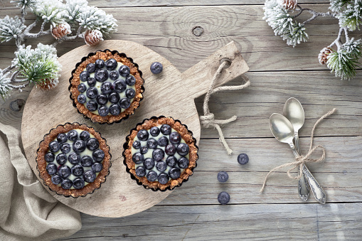 Winter blueberry tarts on wooden table decorated with pine twigs