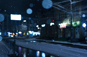 istock Winter blurred background with falling snow on the background of a city street 1301142610