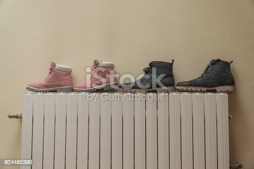 istock Winter boots are dried on the battery near the wall. 924465390