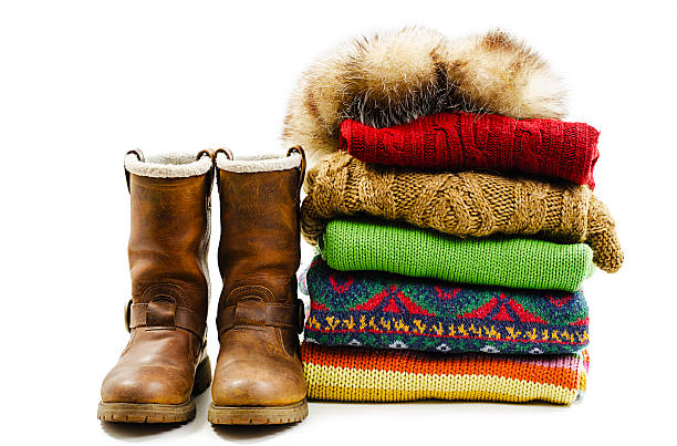 Winter boots, cap and stack of various sweaters. Winter style Winter boots, cap and stack of various sweaters. Winter style. Isolated on white background warm clothing stock pictures, royalty-free photos & images