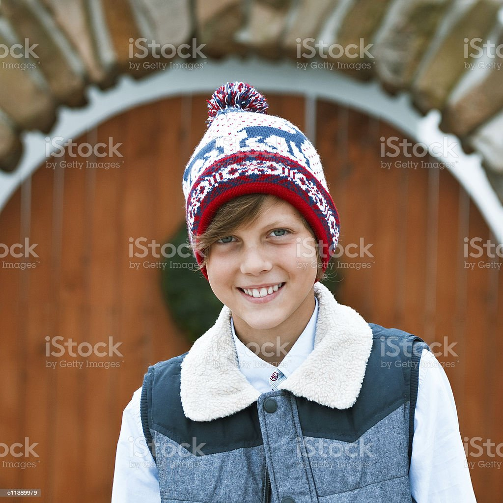 Winter Boy Outdoor portrait of cute boy wearing winter clothes and cap, smiling at camera. 10-11 Years Stock Photo