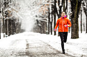 front view of sporty woman jogging  in winter during snowfall on snow covered road in alley with snowcovered trees december january outdoor sports in cold bad weather theme
