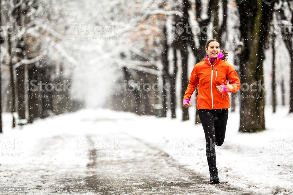 Winter Breaks - 40 years old woman running on country road through alley on cold winter day with snow and frost stock photo