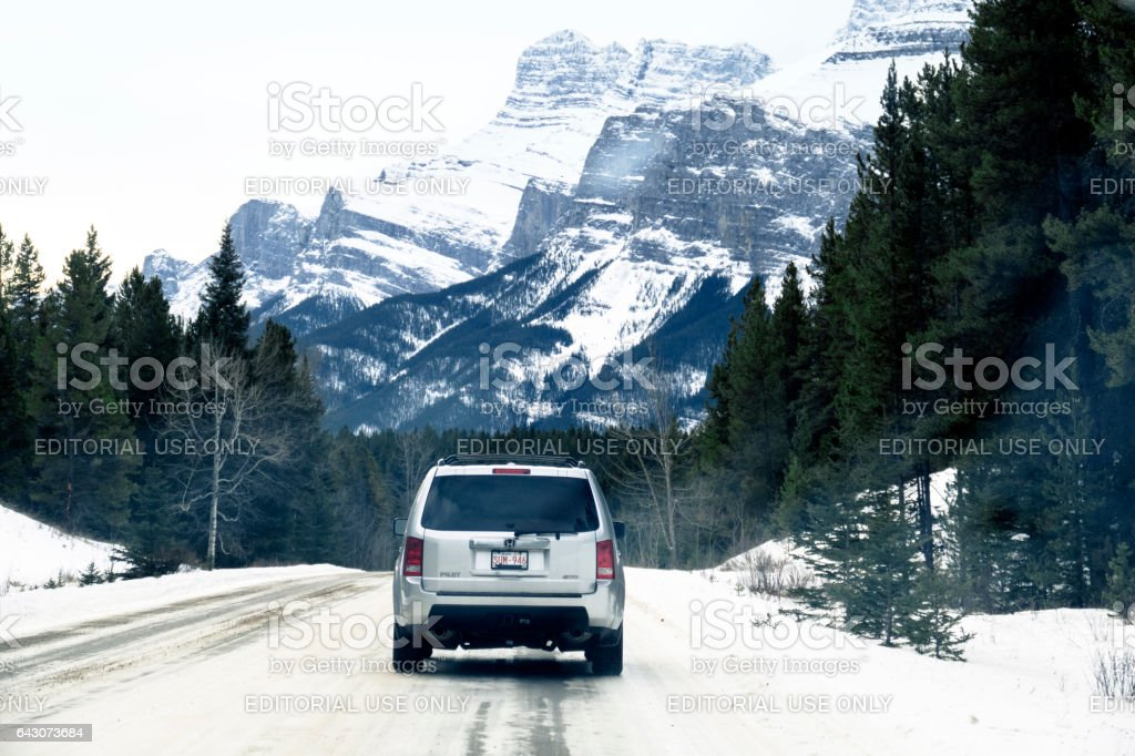 Winter Breaks: Rear view of a SUV Honda Pilot 4WD  driving on a winter road in Banff, Banff National Park,Alberta,Canada stock photo