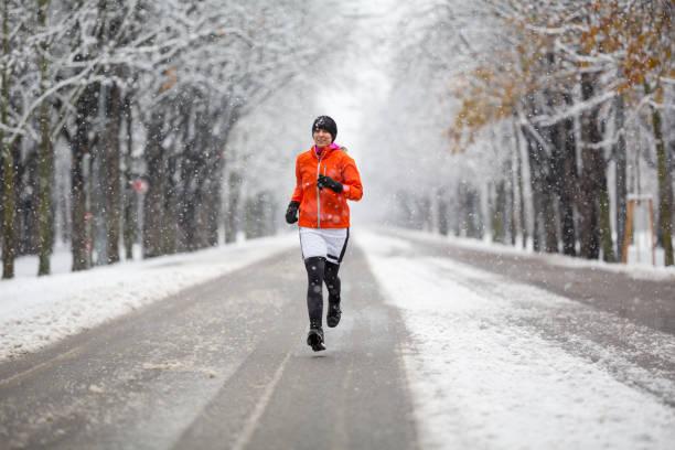 vintern bryter - kvinna jogging i gränd på kall vinterdag klädd med varm kjol över kör byxor - winter austria train bildbanksfoton och bilder