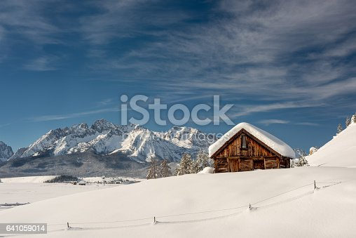 Rustic old wood cabin with a snow covered moutnain range