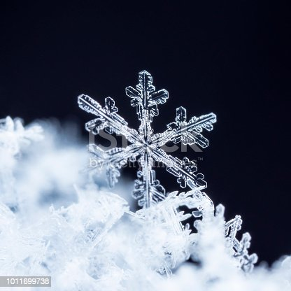 istock winter card, photo real snowflakes on snow 1011699738