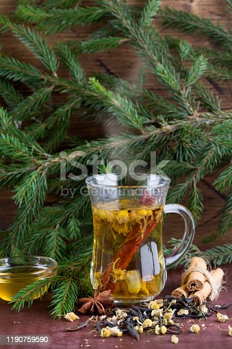Winter chamomile hot tea with honey, cinnamon and christmas tree branch on wood background. christmas decorations, copy space