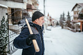 One man, prepared for clean the street full on snow, holding snow shovel.
