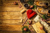 Winter christmas weekend in country cottage (cabin) concept. Boots, hat, hot drinks, candy canes and firewood. Rustic layout, from above (flat lay). Vintage wooden background with free text space.