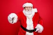 冬クリスマス!成功幸福購入不動産の宿泊施設コンセプトの賃貸料。赤い背景をキーを押したままに分離された伝統コスチューム手袋眼鏡白ひげサンタ