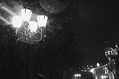 Winter city, snowfall, glowing lantern in the foreground. Monochrome, artificially created noise and grain effect.