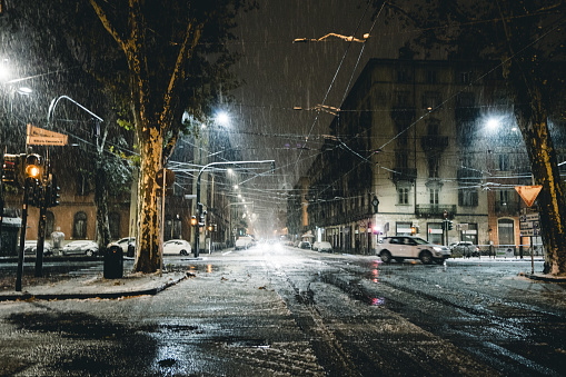 Winter city street in the night under the snow Turin Italy