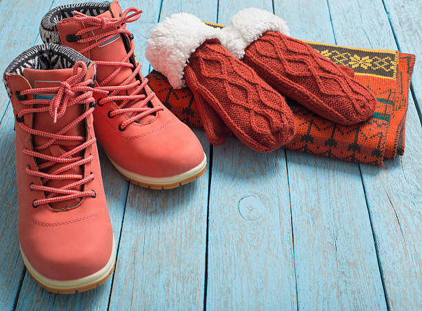 winter clothes and shoes on a wooden background - warm clothing stock photos and pictures