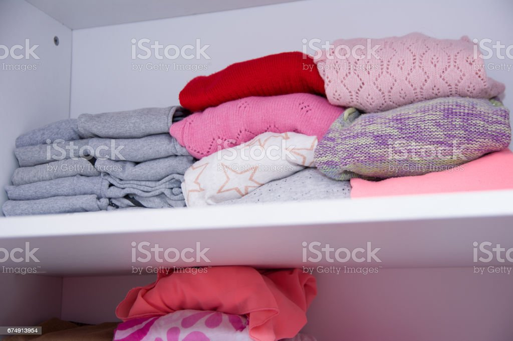 Winter clothes nicely arranged on a shelf. Tidy wardrobe with colorful clothes and accessories. royalty-free stock photo