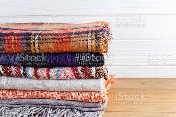 Winter fashion clothing with scarf and blanket with wood background