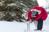 A woman is adjusting a winter coat on her dog.