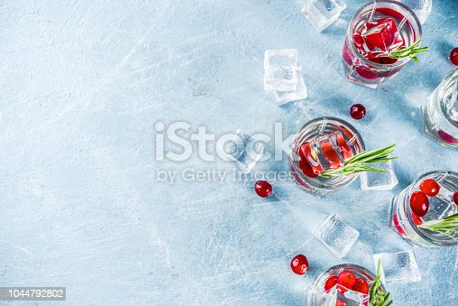 Christmas or New Year winter cranberry cocktail with rosemary, liqueur, gin tonic, on light blue concrete background with ice cubes, fresh berries and rosemary twig copy space