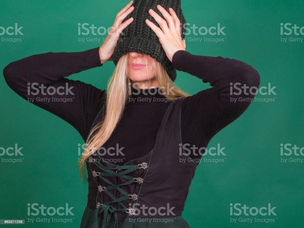 Winter coming. Portrait of blonde with knitted stylish hat covering eyes. stock photo