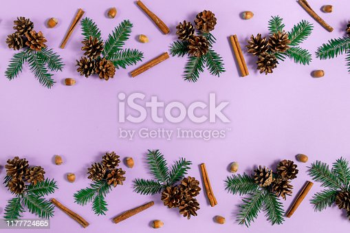 istock Winter composition. Frame made of fir tree branches, pine, acorn and cinnamon on violet background. Autumn, fall, winter concept. Flat lay, top view, copy space 1177724665