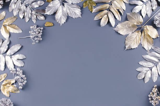 winter-konzept flach legen mit goldenen und silbernen blättern. weihnachten rahmenhintergrund - laub winter stock-fotos und bilder
