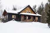 Cottage in the winter with overcast skies and after a fresh snowfall