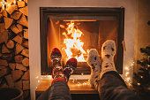 Lazy winter day in front of fire in fireplace. Human legs in Christmas socks in front of fireplace.