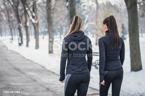 Two women, young fit girls training on a cold winter day outdoors, rear view.