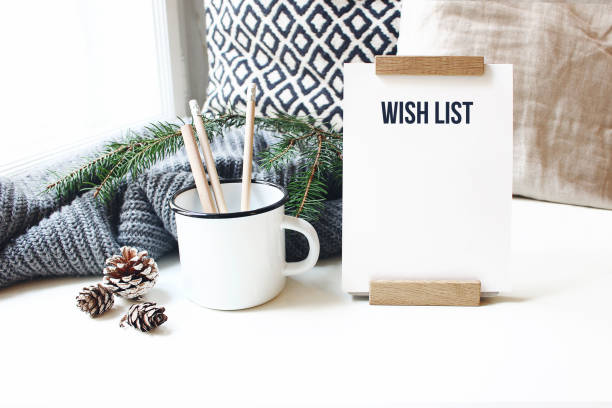 winter desktop still life scene. wish list card, board and wooden pencils in mug standing near window on white table background. christmas concept. pine cones and fir branch on wool plaid. - wish imagens e fotografias de stock