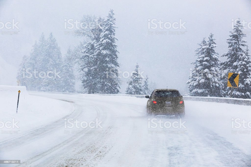 Winter Driving: Car Traveling on Icy Freeway Montana Snow Storm stock photo