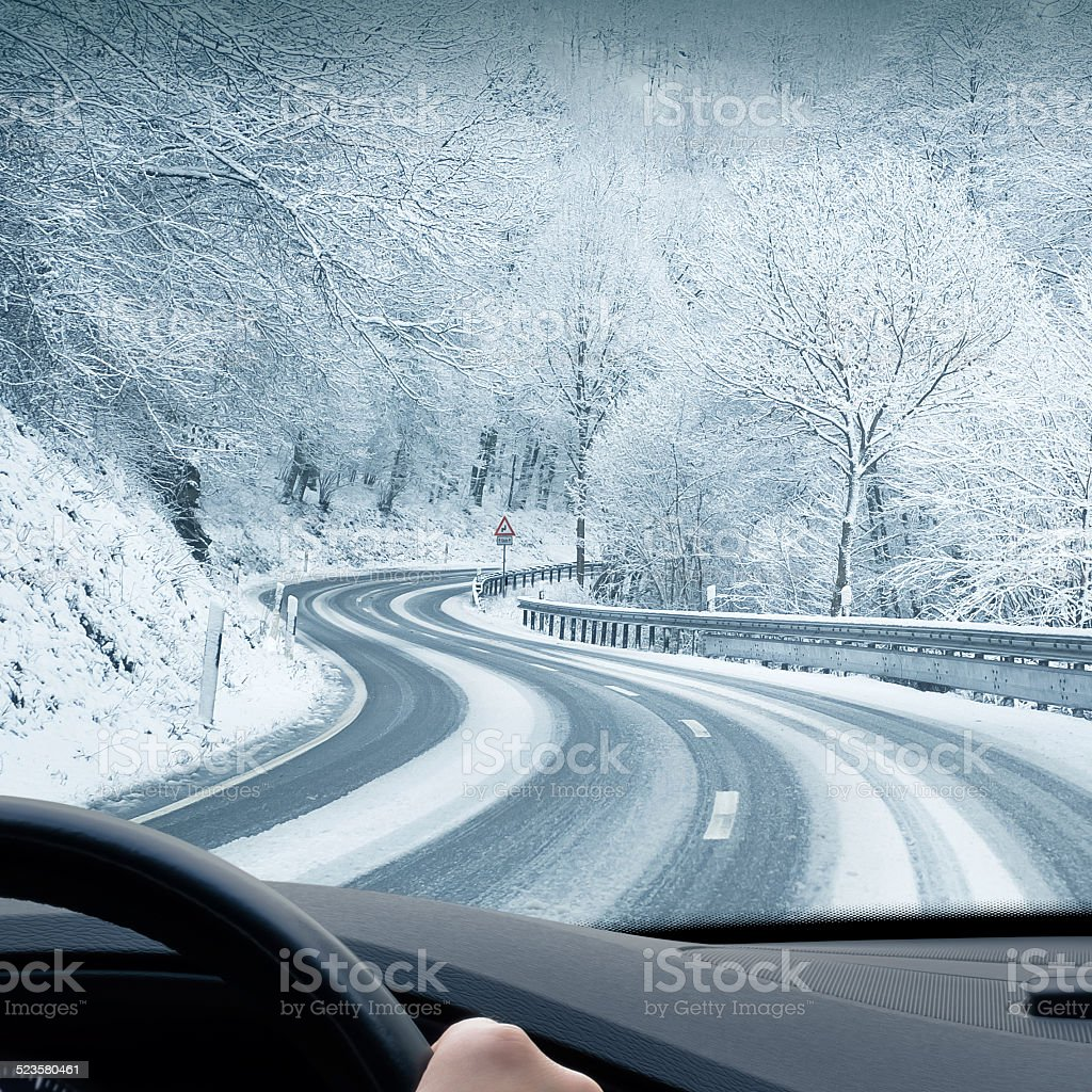 Winter Driving - Curvy Snowy Country Road Curvy winter country road leading through a mountain landscape. Blizzard Stock Photo