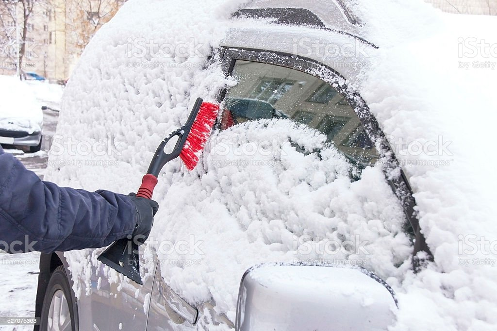 Winter driving. Hand of man is cleaning car from snow. stock photo