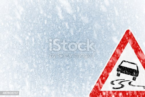 istock Winter driving - ice covered windshield with warning sign 482803237
