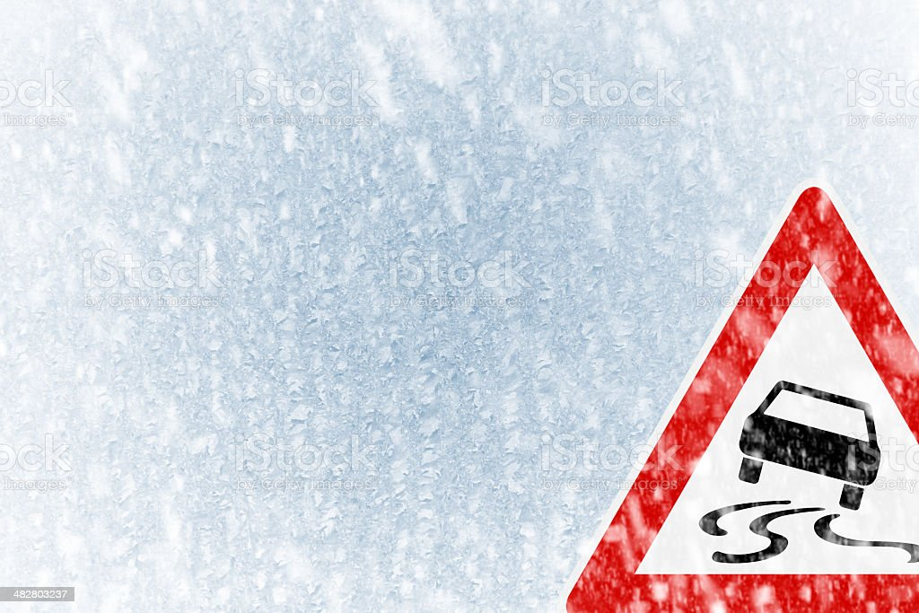 Winter driving - ice covered windshield with warning sign stock photo