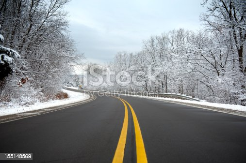 The center of a winding road on a winter day with fresh snow. The road is clear for safe driving.