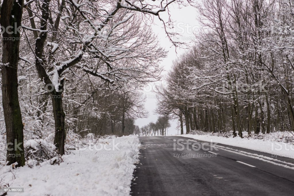 Winter driving problems, snow and ice. Extreme winter series.  Close up of a  road in cold winter conditions, a road cleared from the snow. stock photo