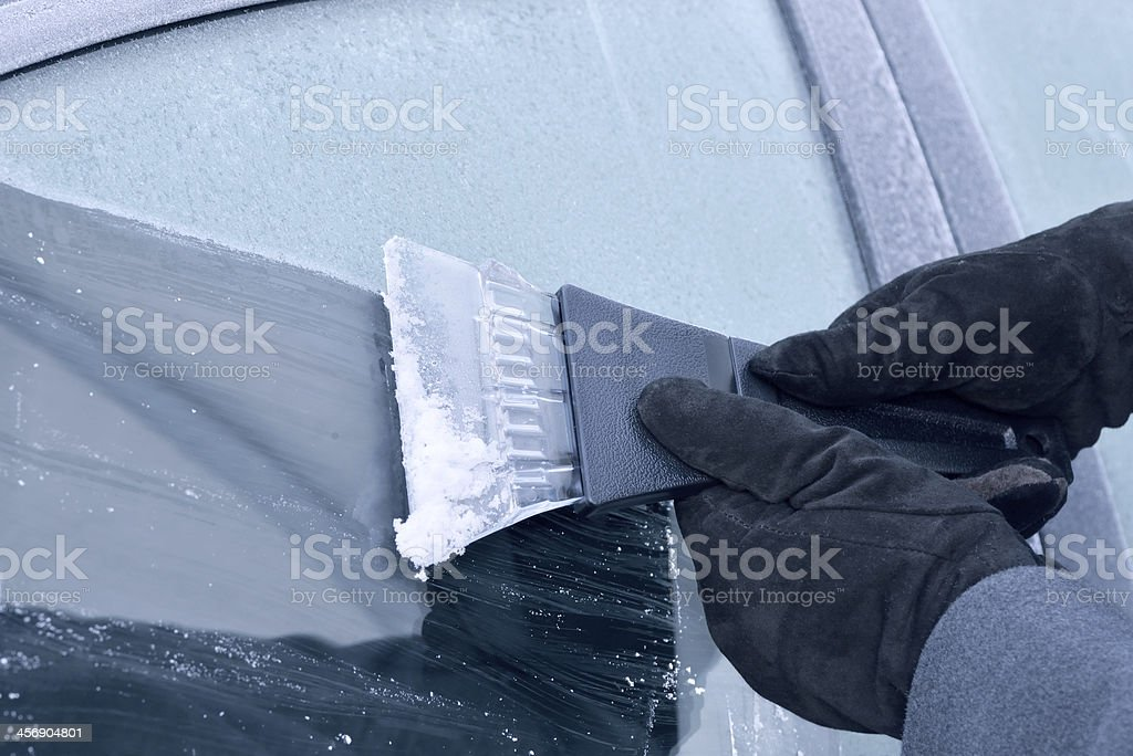 winter driving - scraping ice from a car window stock photo