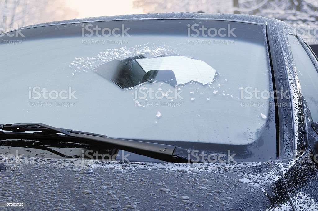 winter driving - scraping ice from a windshield stock photo