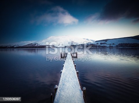 Snow covering a wooden jetty and the hills beyond the shore of Loch Earn in the Trossachs, Scotland. Photographed at dusk in January.