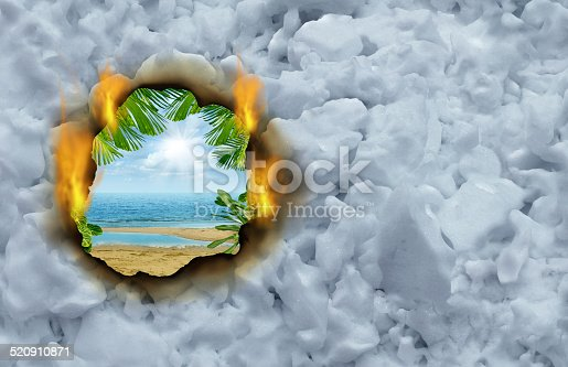 Winter escape concept as a burning hole on a cold winter snow background revealing a hot tropical beach and ocean scene  as a traval and vacation symbol.