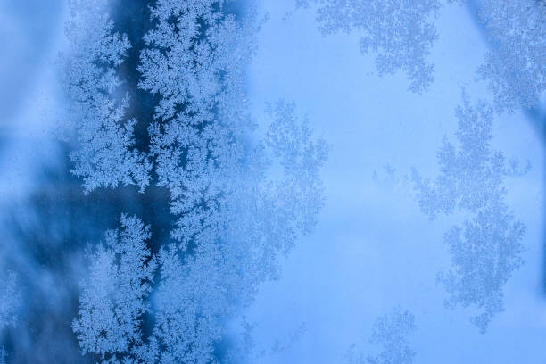 winter evening patterns on a glass window close up blue bewitching background stock photo