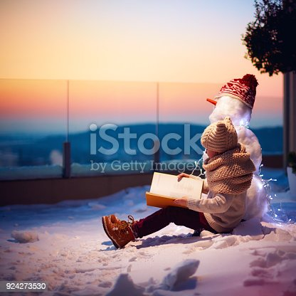 istock winter fairy tale. young boy, kid reading interesting book to his friend snowman at the backyard 924273530